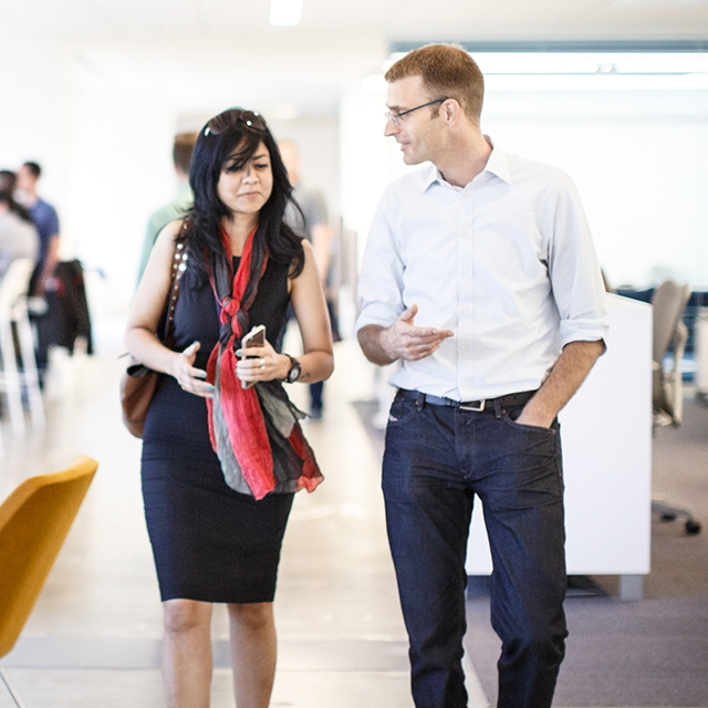 Man and woman walking together through a building and talking.
